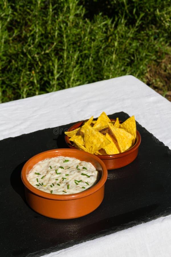Immersion d'aubergine dans la cuvette en céramique avec des puces de tortilla Dehors sur s image libre de droits