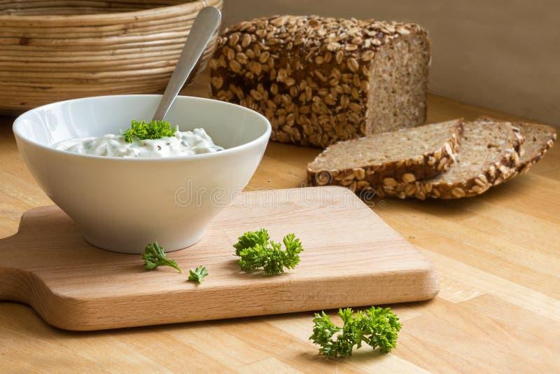Immersione della ricotta con le erbe in una ciotola ed in un pane rustico nel BAC immagine stock