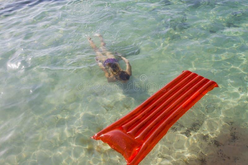 Immersione subacquea della donna sotto l'acqua verso un lilo fotografia stock