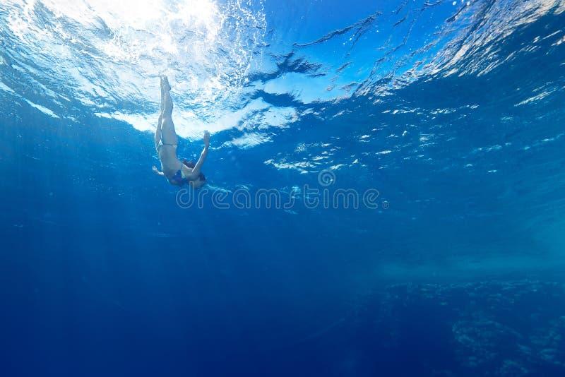 Immersione subacquea della ragazza sotto il mare immagine stock