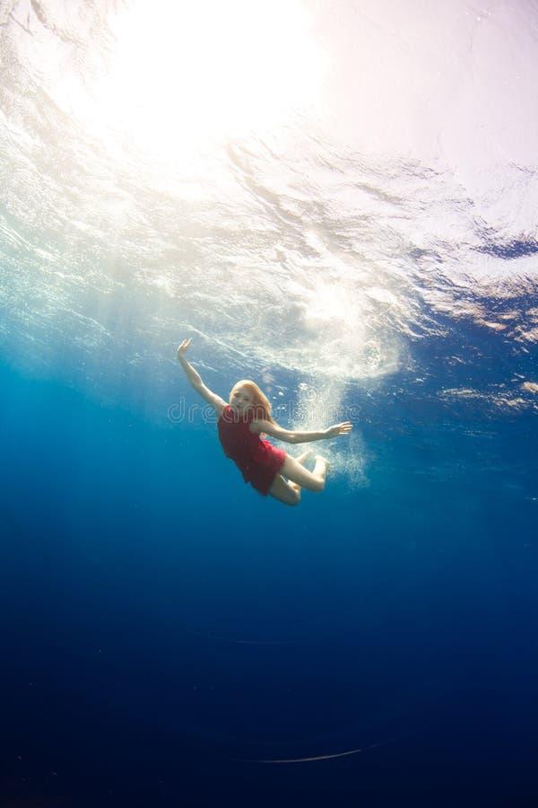 Immersione subacquea della ragazza sotto il mare immagini stock