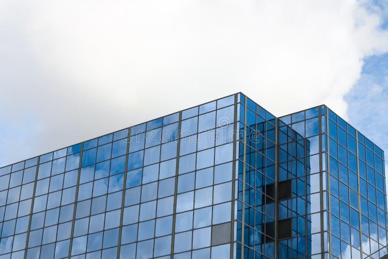 Immeuble de bureaux avec la surface en verre reflétant le ciel nuageux bleu photographie stock