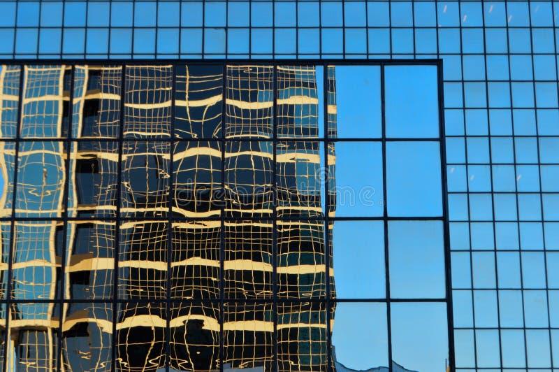 Immeuble de bureaux en verre moderne avec la réflexion du modèle et des lignes lumière bleue d'heure images libres de droits