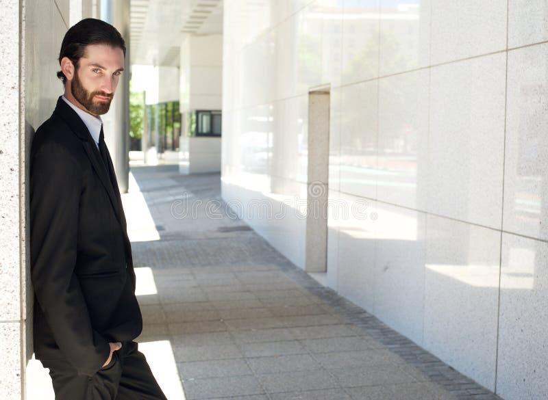 Immeuble de bureaux extérieur debout de jeune homme d'affaires à la mode photographie stock
