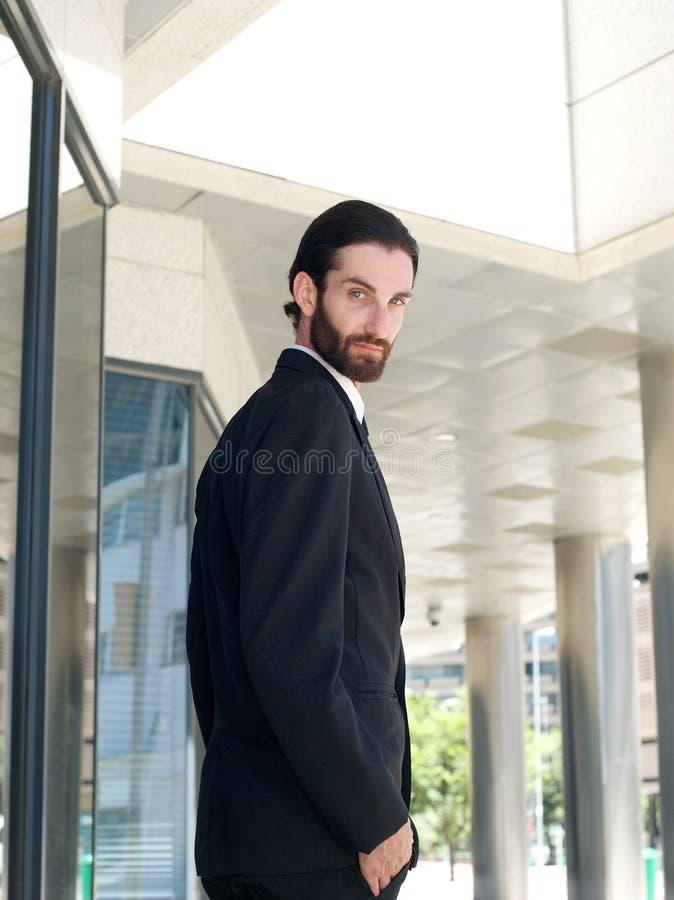 Immeuble de bureaux extérieur debout de jeune homme d'affaires attirant photo libre de droits