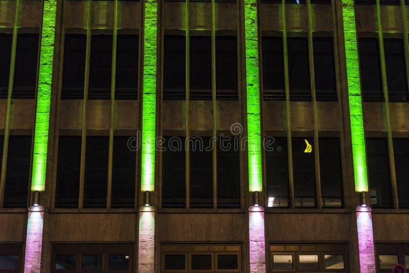 Immeuble de bureaux la nuit avec les feux verts sur sa façade photo libre de droits
