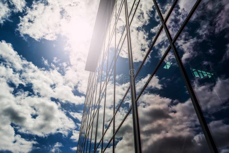 Immeuble de bureaux moderne avec des nuages réfléchissant sur la façade en verre photographie stock libre de droits