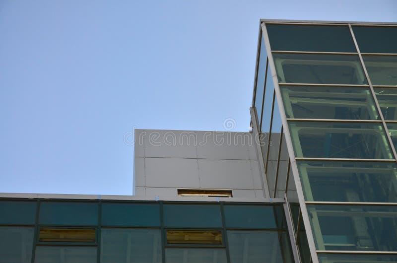 Immeuble de bureaux moderne avec les murs transparents en verre contre le ciel bleu image libre de droits