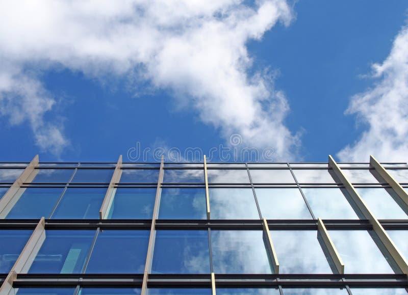 Immeuble de bureaux moderne avec les vitraux reflétés reflétant un ciel bleu lumineux et des nuages blancs photos libres de droits