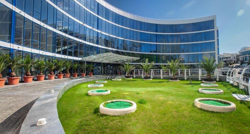 Immeuble de bureaux moderne avec une façade en verre et une pelouse verte photo libre de droits