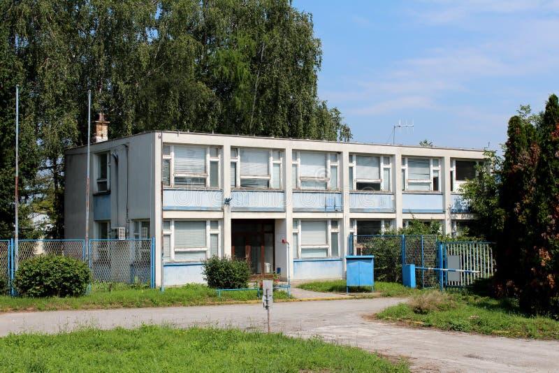 Immeuble de bureaux négligé avec les fenêtres délabrées et les portes entourées avec l'herbe non coupée et arbres grands à l'arri photos libres de droits
