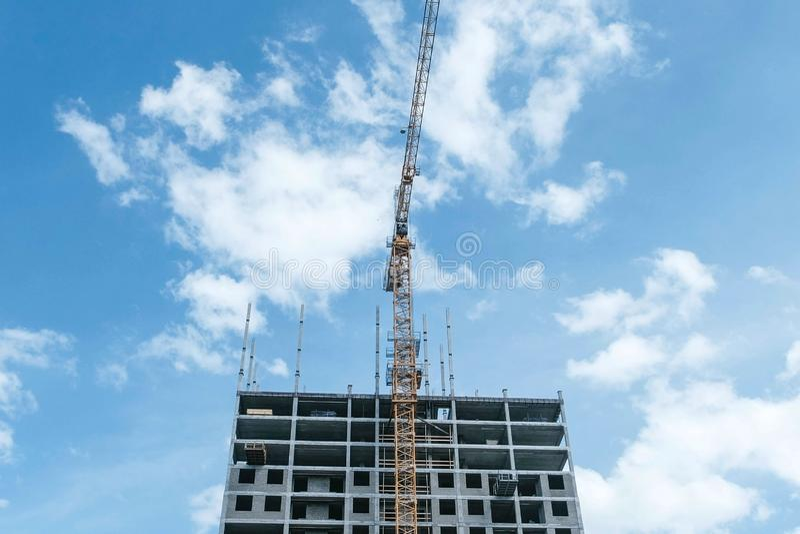 Immeuble en construction à plusiers étages avec une grue de bâtiment sur un fond de ciel photographie stock