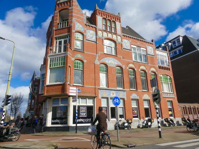 Immeuble historique de brique rouge à la Haye avec le restaurant de point de sushi photo stock