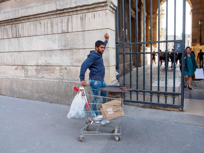 Immigrant verkauft Kastanien vor dem Lourve, Paris, Frankreich stockfotos
