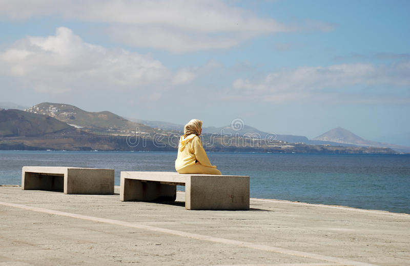 Immigrant woman sitting and looking at the sea. In Spain stock image