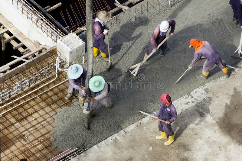 Immigrant workers at construction worksite. Immigrant workers making reinforcements for concrete foundations in Kuala Belait, Brunei royalty free stock image
