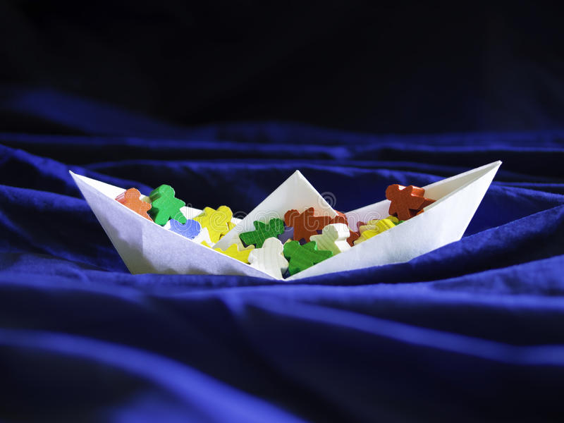Immigration emigration migration concept, paperboat with meeples stock images