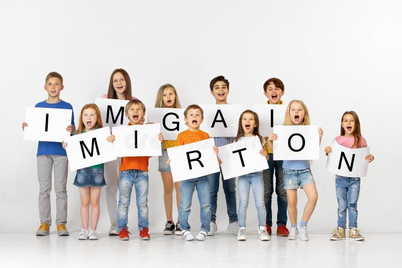 immigration Groupe d'enfants avec bannières d'isolement dans le blanc image stock