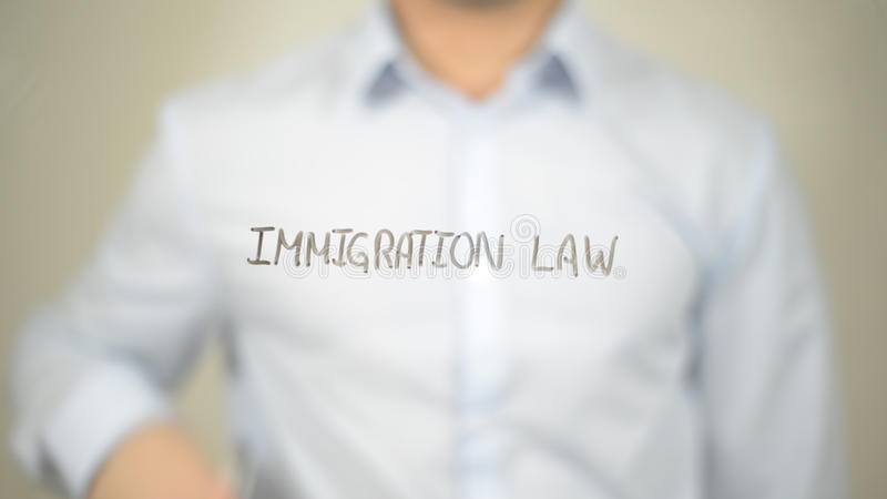 Immigration Law, man writing on transparent screen. High quality stock photography