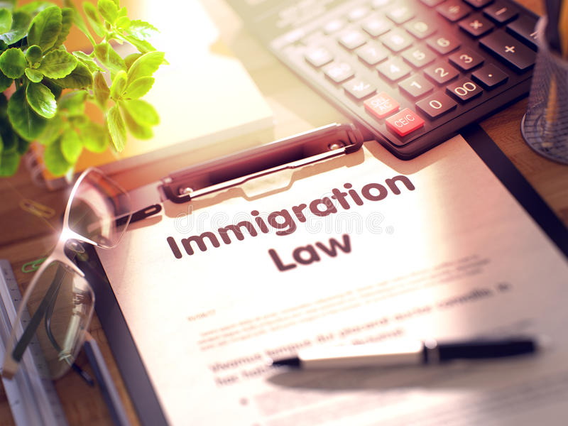Immigration Law - Text on Clipboard. 3d. Immigration Law on Clipboard. Wooden Office Desk with a Lot of Business and Office Supplies on It. 3d Rendering stock image