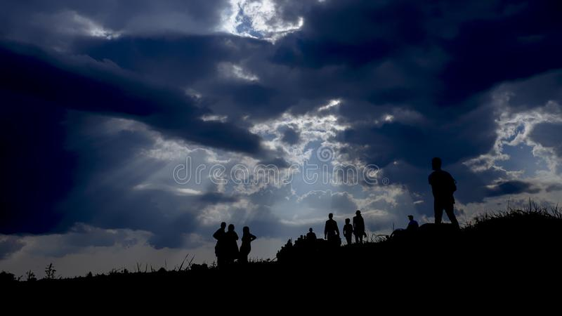 Immigration of people and blue sky. Sun rays illuminate people. Immigration of people. Blue sky with dark clouds royalty free stock photos