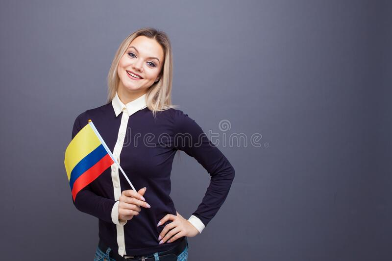 Immigration and the study of foreign languages, concept. A young smiling woman with a Colombia flag in her hand. Girl waving a Colombia flag on a gray stock image