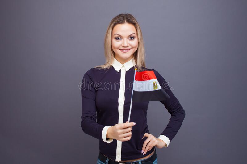 Immigration and the study of foreign languages, concept. A young smiling woman with a Egypt flag in her hand. Girl waving a Egyptian flag on a gray background stock photography