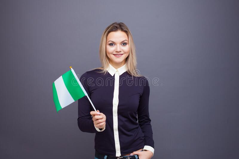 Immigration and the study of foreign languages, concept. A young smiling woman with a Nigeria flag in her hand. stock photos