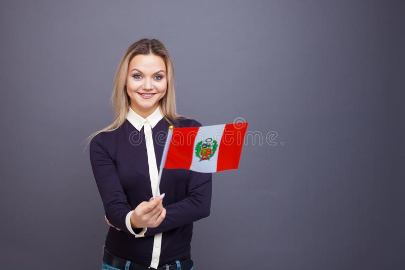 Immigration and the study of foreign languages, concept. A young smiling woman with a Peru flag in her hand royalty free stock photography