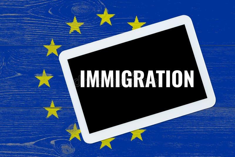 Immigration, texte sur le PC de comprimé au-dessus du drapeau d'Eu photos stock