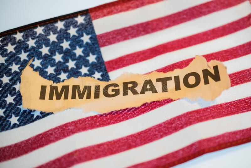 Immigration word laying on American Flag. Immigration word on torn vintage paper laying on an American Flag stock images