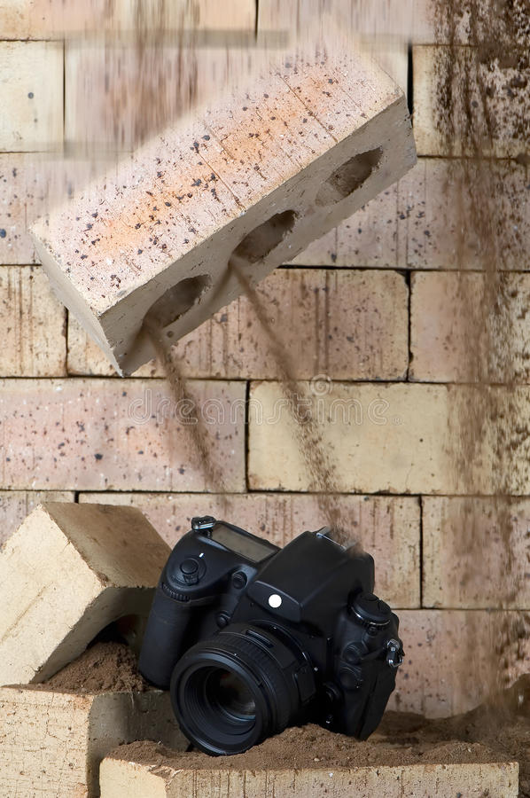 Imminent destruction. A falling brick is about to demolish a camera royalty free stock image