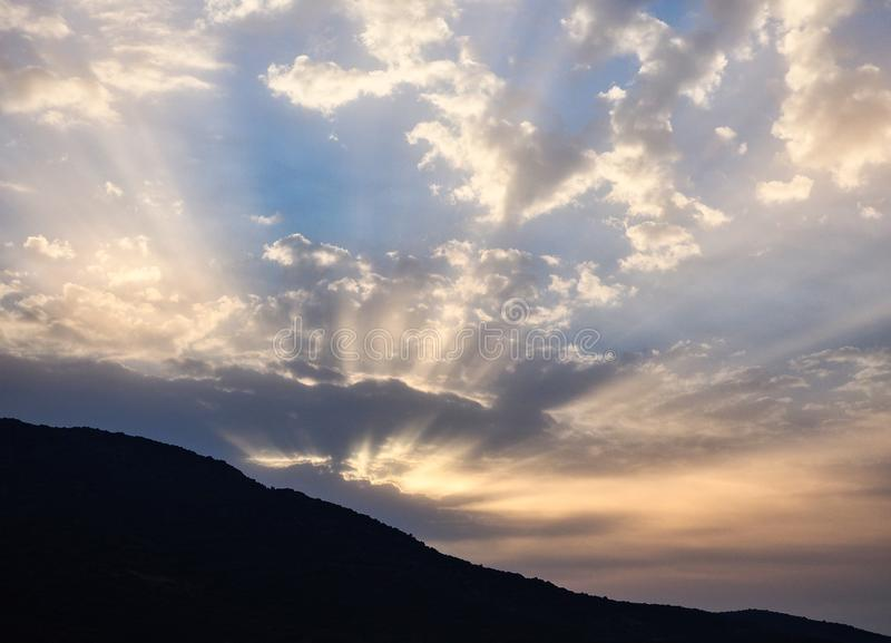 Sunrise Rays Struggling Through Dark Clouds. Imminent sunrise over dark mountain, with sun rays struggling to shine through dense grey clouds sitting over the royalty free stock image