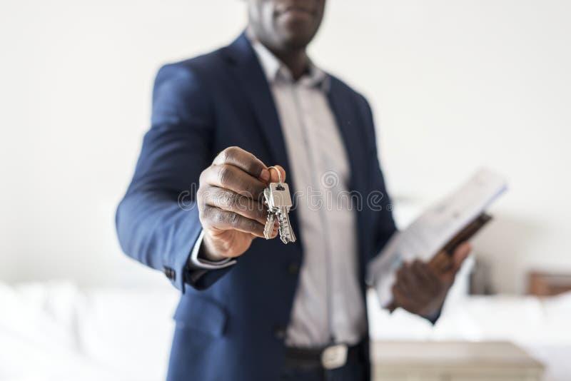 Immobilienagentur, die den Hausschlüssel übergibt lizenzfreie stockfotografie