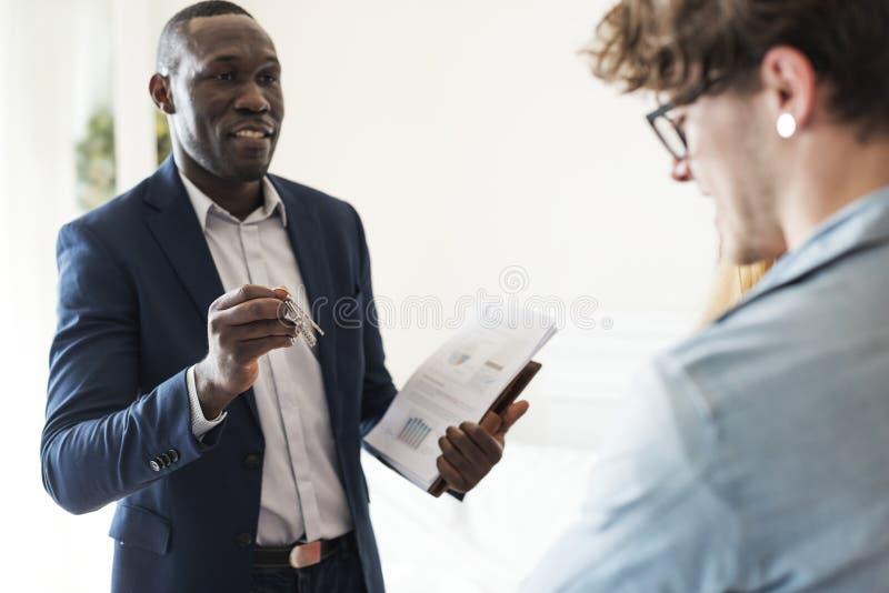 Immobilienagentur, die den Kunden den Hausschlüssel übergibt lizenzfreies stockfoto