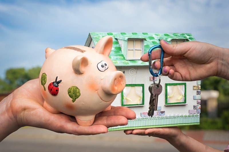 Immobilienagentur, die Hausschlüssel und -Musterhaus gibt stockfotos