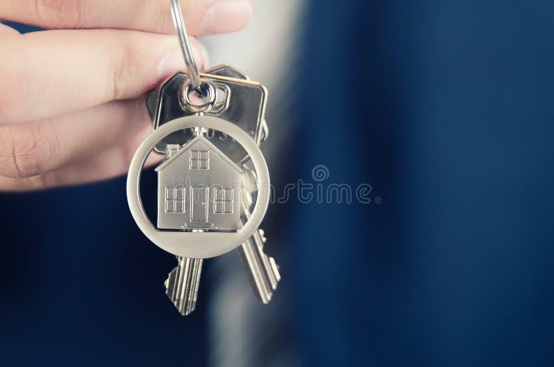Immobilienagentur, die Schlüssel des neuen Wohnungsabschlusses hochhält lizenzfreie stockfotografie