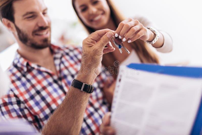 Immobilienagentur, die Schlüssel zu den Paaren von Kunden gibt lizenzfreie stockfotos