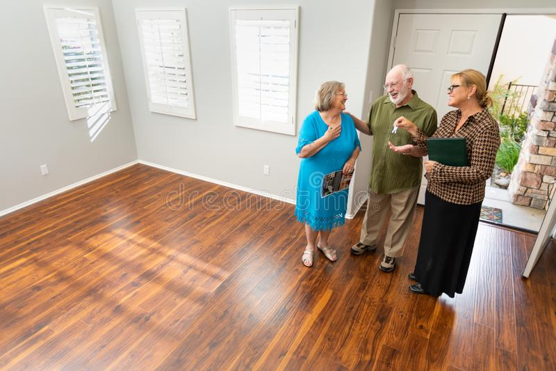 Immobilienagentur Handing New House befestigt zu den älteren Paaren stockbilder