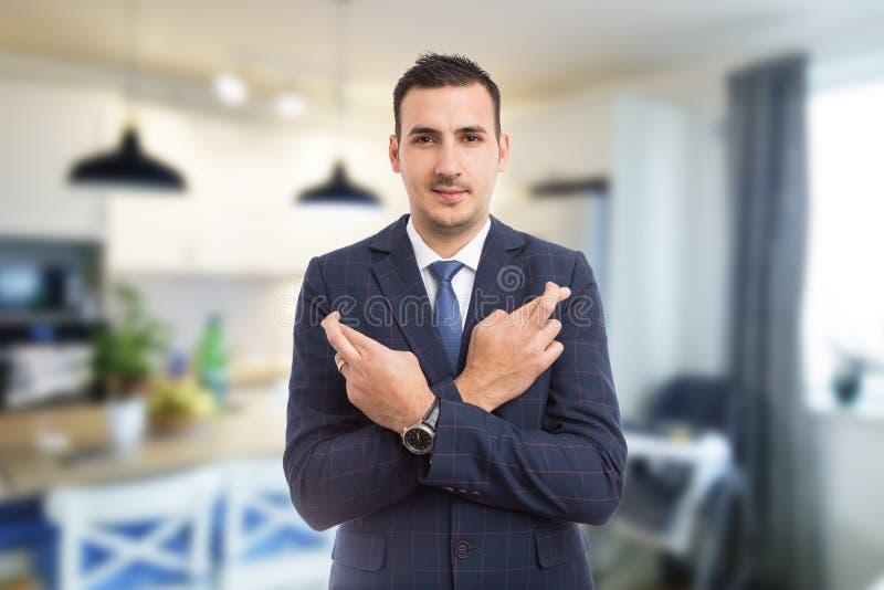 Immobilienagentur mit den Fingern zuhause gekreuzt auf Hintergrund lizenzfreie stockbilder