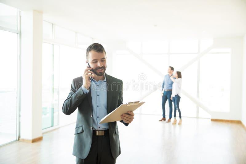 Immobilienagentur Using Mobile Phone am neuen Haus stockbild