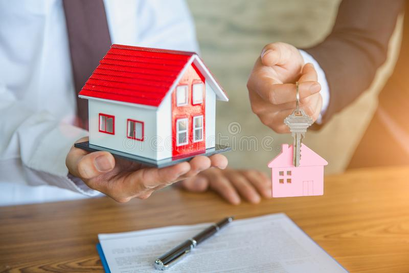 Immobilienagenturholding-Hausmodell und Schl?ssel, unterzeichnender Vertrag des Kunden, zum von Immobilien des Hauses, der Versic lizenzfreies stockfoto