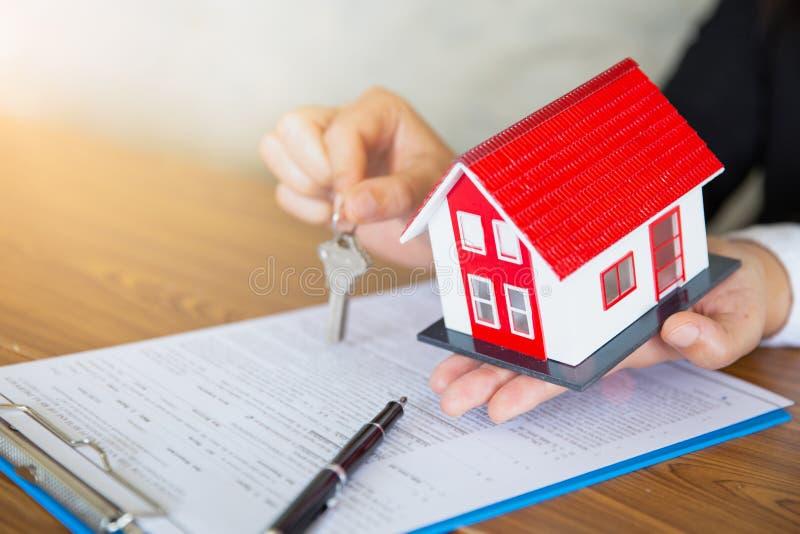 Immobilienagenturholding-Hausschl?ssel zu seinem Kunden, nachdem Vertragsvereinbarung im B?ro, das Konzept f?r Immobilien unterze stockfotos