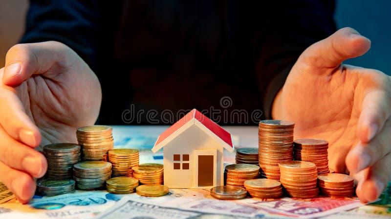 Immobilieninvestition Hände, die Stapel der Münzen schützen stockfotos
