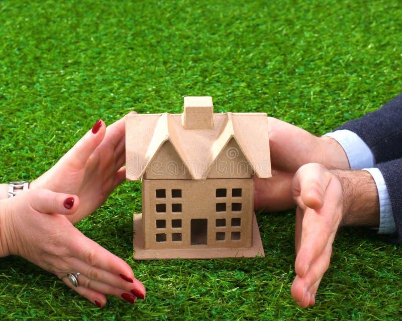 Immobilienkonzept - Hände einer jungen Frau umgeben ein weißes Ausschnitthaus über grünem Gras stockfoto