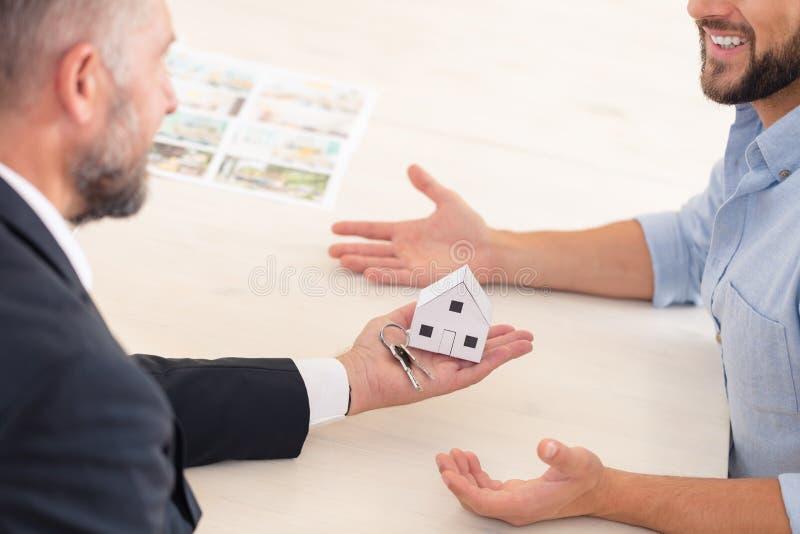 Immobilienmakler, der Tasten gibt lizenzfreies stockbild