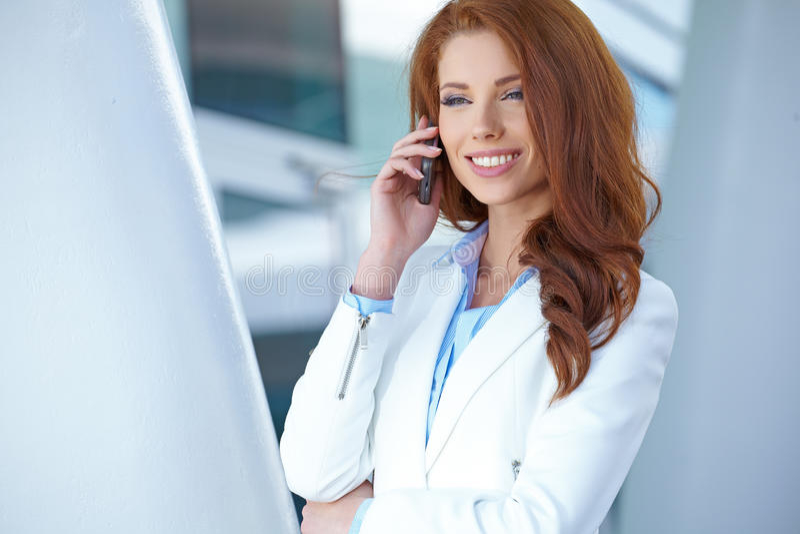 Immobilienmaklerfrau am Telefon lizenzfreies stockbild