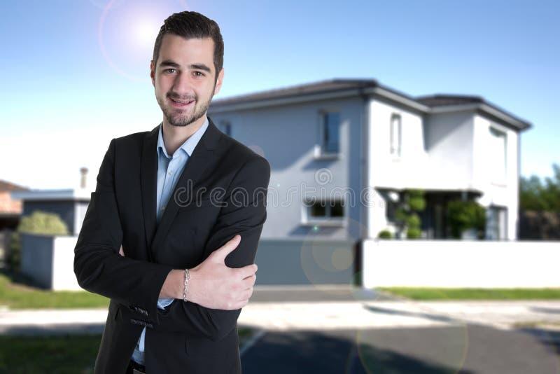 Immobilienmannfront des neuen Hauses zu den Verkaufsmietporträtarmen kreuzte stockfotografie