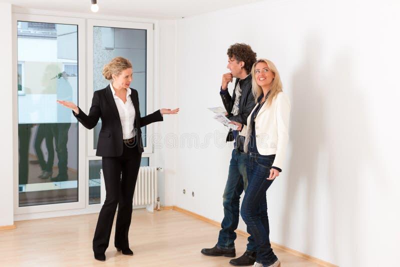 Junge Paare, die nach Immobilien mit weiblichem Grundstücksmakler suchen stockfoto