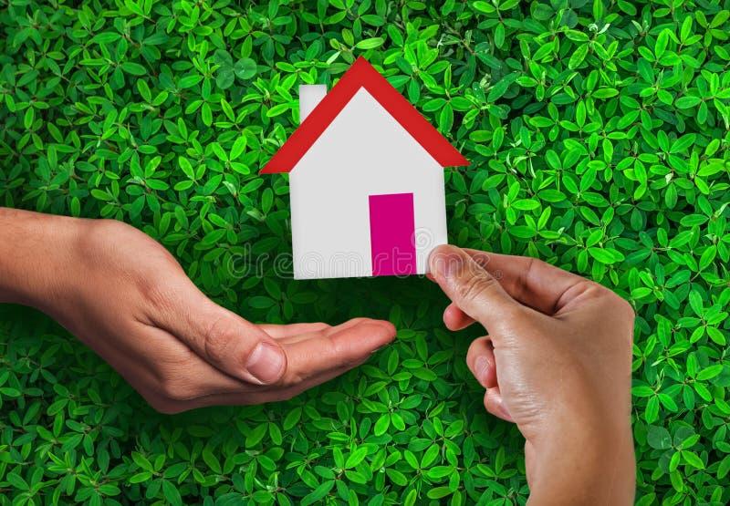 Immobiliers et logement de la publicité de couverture de dommages avec la main de femme tenant la maison de papier la déposant da photo stock